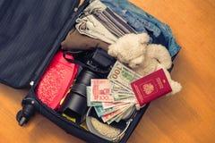 Valigia con l'orsacchiotto di cose e un passaporto straniero Fatture asiatiche del cento-dollaro e dei soldi per il viaggio Conce immagini stock