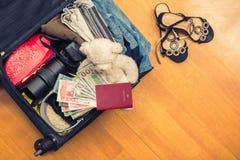 Valigia con l'orsacchiotto di cose e un passaporto straniero Fatture asiatiche del cento-dollaro e dei soldi per il viaggio Conce fotografia stock