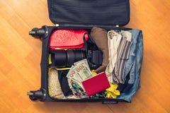Valigia con le cose e un passaporto straniero Fatture asiatiche del cento-dollaro e dei soldi per il viaggio Concetto fotografia stock libera da diritti