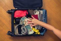 Valigia con le cose e un passaporto straniero Fatture asiatiche del cento-dollaro e dei soldi per il viaggio Concetto fotografia stock