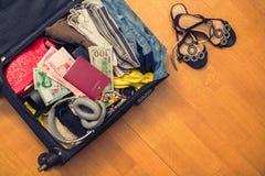 Valigia con le cose e un passaporto straniero Fatture asiatiche del cento-dollaro e dei soldi per il viaggio Concetto immagini stock