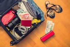 Valigia con le cose e un passaporto straniero Fatture asiatiche del cento-dollaro e dei soldi per il viaggio Concetto immagini stock libere da diritti