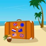 Valigia d'annata con gli autoadesivi della bandiera disposti sulla spiaggia tropicale con il mare pacifico Fotografia Stock Libera da Diritti