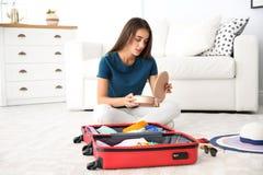 Valigia dell'imballaggio della giovane donna a casa fotografia stock