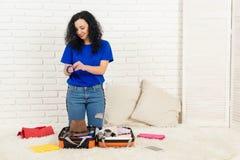 Valigia felice dell'imballaggio della giovane donna a casa fotografie stock libere da diritti