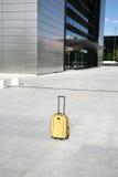 Valigia gialla davanti alla costruzione di affari Fotografia Stock