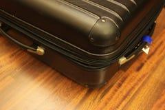 Valigia nera sul pavimento di legno Fotografie Stock Libere da Diritti