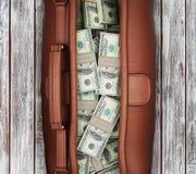Valigia in pieno dei dollari su un fondo di legno Fotografia Stock Libera da Diritti