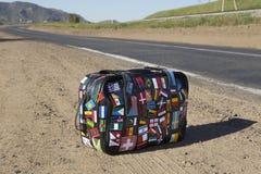 Valigia sul bordo della strada Fotografia Stock
