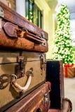 Valigie d'annata con il fondo delle luci dell'albero di Natale e del presente fotografia stock