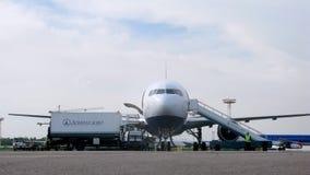 Valigie nel salotto di partenza dell'aeroporto, aeroplano nel fondo, concetto di vacanze estive archivi video