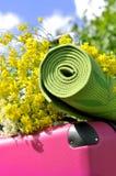 Valise avec les fleurs et le tapis de yoga Images stock