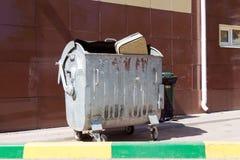 Valise beige jetée dans une poubelle en métal se tenant contre un wa Photographie stock