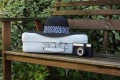 Valise blanche, le vieil appareil-photo et chapeau sur un banc dans un jardin Photo stock