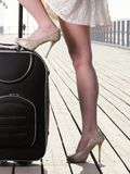 Valise d'amarrage de mer de pied de fille de femme sur une jetée Photographie stock libre de droits