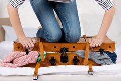 Valise d'emballage de jeune femme sur le lit Photographie stock