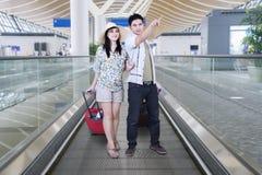 Valise de transport de jeunes couples sur l'escalator Images stock