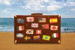 Valise de voyage avec des autocollants sur le fond de mer Image stock