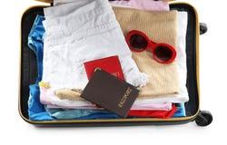 Valise emballée avec des vêtements et des passeports sur le fond blanc image stock