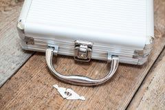 Valise fermée d'aluminium avec des clés sur le plancher Images stock