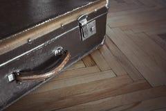 Valise fermée de vintage sur le vieux parquet Foyer sélectif Image libre de droits