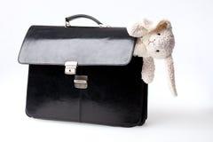 Valise noire avec le jouet blanc de lapin Photographie stock