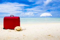 Valise rouge à la plage Photos libres de droits