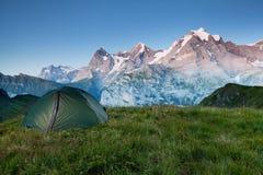 Vallée alpine rougeoyant par lumière du soleil Tente verte dans le pâturage Attraction touristique populaire Scène dramatique et  image libre de droits