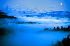 Vallée brumeuse sous le ciel de lune Photos stock