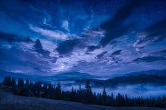 Vallée de montagne avec des étoiles dans un ciel nocturne nuageux images stock