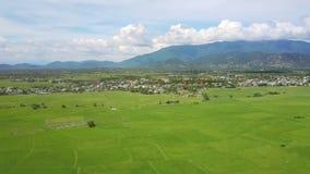 Vallée verte et village contre le panorama de montagnes banque de vidéos