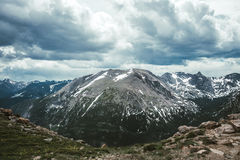 Vallées de montagne et crêtes de Rocky Mountains Nuages sombres de neige Image stock