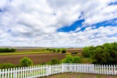 Valla de estacas, tierras de labrantío, y nubes blancas imagen de archivo libre de regalías