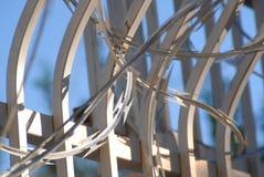 Valla de seguridad con el upclose del cielo azul del alambre de la maquinilla de afeitar Foto de archivo libre de regalías