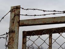 Valla de seguridad y puerta viejas y oxidadas con alambre de p?as en el top imágenes de archivo libres de regalías