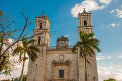 Valladolid, Mexico. Cathedral de San Servasio during the day in Valladolid the city in Yucatan, Mexico. Cloudy sky and palm trees Stock Photos
