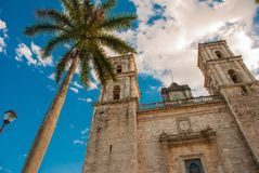 Valladolid, Mexico. Cathedral de San Servasio during the day in Valladolid the city in Yucatan, Mexico. Cloudy sky and palm trees Stock Image