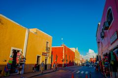 VALLADOLID MEXICO - NOVEMBER 12, 2017: Oidentifierat folk som går på det fria av färgrika byggnader i en mexikan Arkivbild