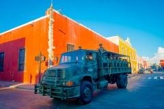 VALLADOLID MEXICO - NOVEMBER 12, 2017: Utomhus- sikt av en militär lastbil omkring av färgrika byggnader i en mexikan Arkivbild