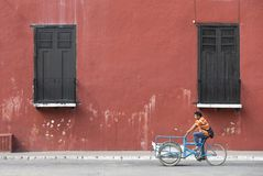 Mexican man on a bike in front of a red wall Stock Photos