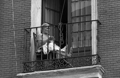 VALLADOLID, SPAIN - JULY, 1979. An elderly woman sewing on the balcony of his house to avoid heat on July, 1979 in Valladolid, Spain Royalty Free Stock Photo