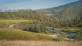 Valle con un fiume e una strada principale nelle montagne verdi Fotografie Stock