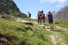 Valle d`Aosta, Italy, August 19 2018: group of hikers walking on italian alps. Valle d`Aosta, Italy, August 19 2018: group of hikers on italian alps Royalty Free Stock Photos