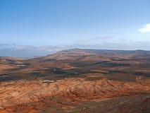 Valle de la montaña con los edificios y los pueblos blancos entre las viejas cuestas volcánicas Tierra roja y campos verdes Foto de archivo