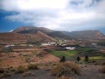 Valle de la montaña con los edificios y los pueblos blancos entre las viejas cuestas volcánicas Tierra roja y campos verdes Fotografía de archivo
