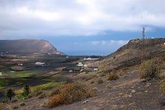 Valle de la montaña con los edificios y los pueblos blancos entre las viejas cuestas volcánicas Tierra roja y campos verdes Imagen de archivo libre de regalías