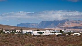 Valle de la montaña con los edificios y los pueblos blancos entre las viejas cuestas volcánicas Tierra roja y campos verdes en el Imagen de archivo