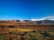 Valle de la montaña con los edificios y los pueblos blancos entre las viejas cuestas volcánicas Tierra roja y campos verdes en el Fotos de archivo libres de regalías