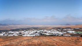 Valle de la montaña con los edificios y los pueblos blancos entre las viejas cuestas volcánicas Tierra roja y campos verdes en el Foto de archivo libre de regalías