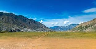 Valle de la montaña con un pueblo lejos la república de Altai, Rusia fotos de archivo